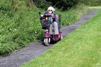 Marguerite with mobility scooter using the current hard path along willow path